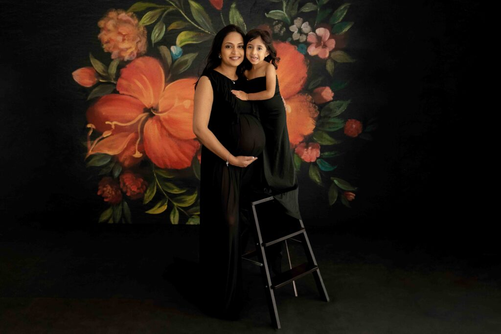 An expectant mum and her young daughter both wearing black dresses posing for a photographer at her maternity photoshoot