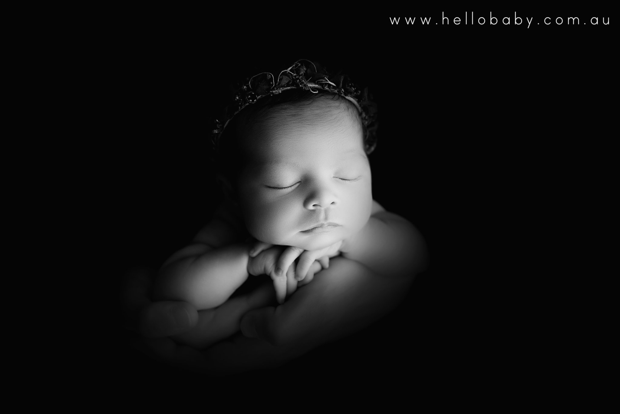 A newborn baby girl sleeping resting her chin on her hands held in her father's safe hands