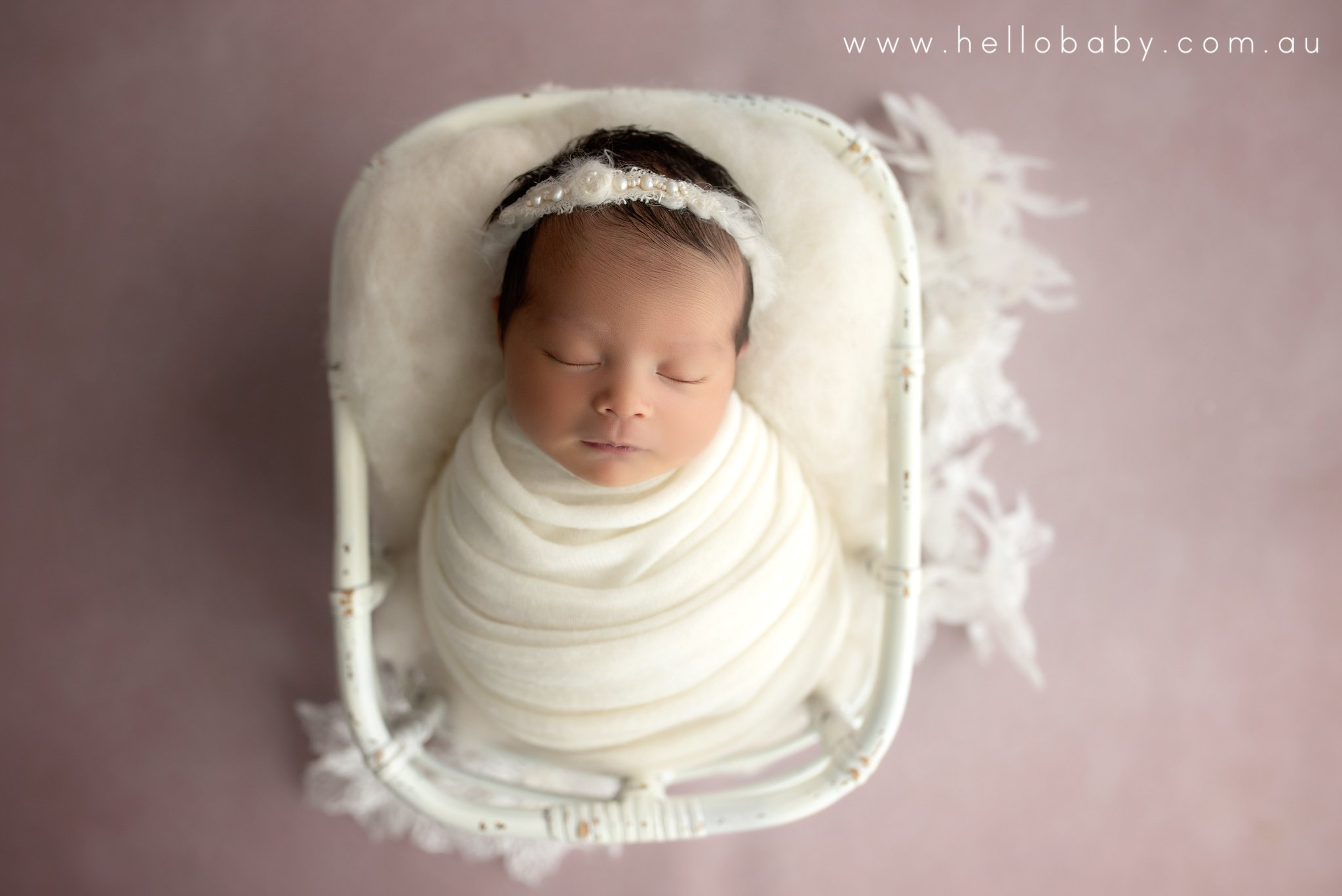 Baby girl wrapped in a white wrap placed in a white basket surrounded by white flowers on a pink floor