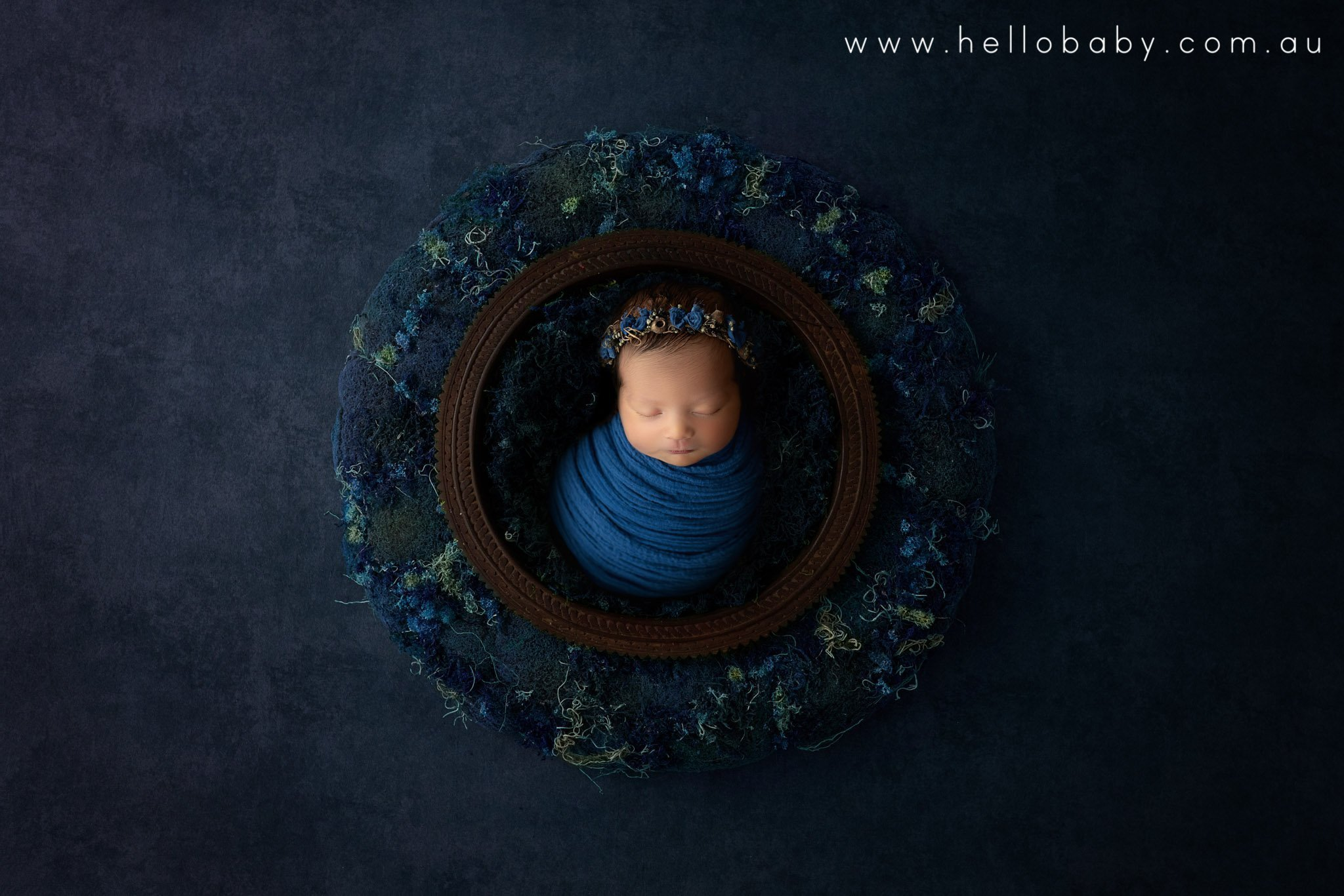 A newborn baby wrapped in blue placed in a dark brown wooden bowl in a blue wreath on a blue mat