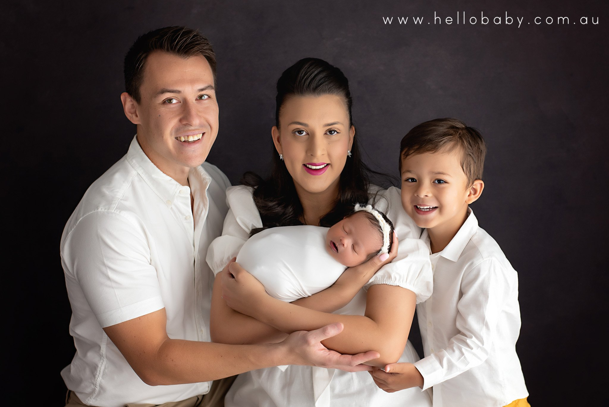 A gorgeous family image showing mum holding her newborn baby girl with dad and their little son cuddling up to her from each side