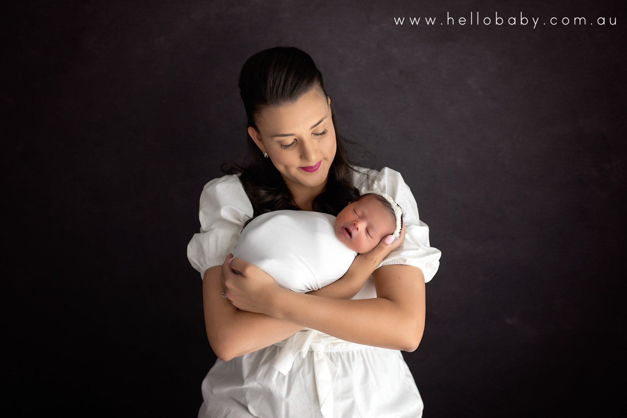 A new mum holding her brand new baby girl. Mum is wearing a simple yet elegant white dress while baby is wrapped in white