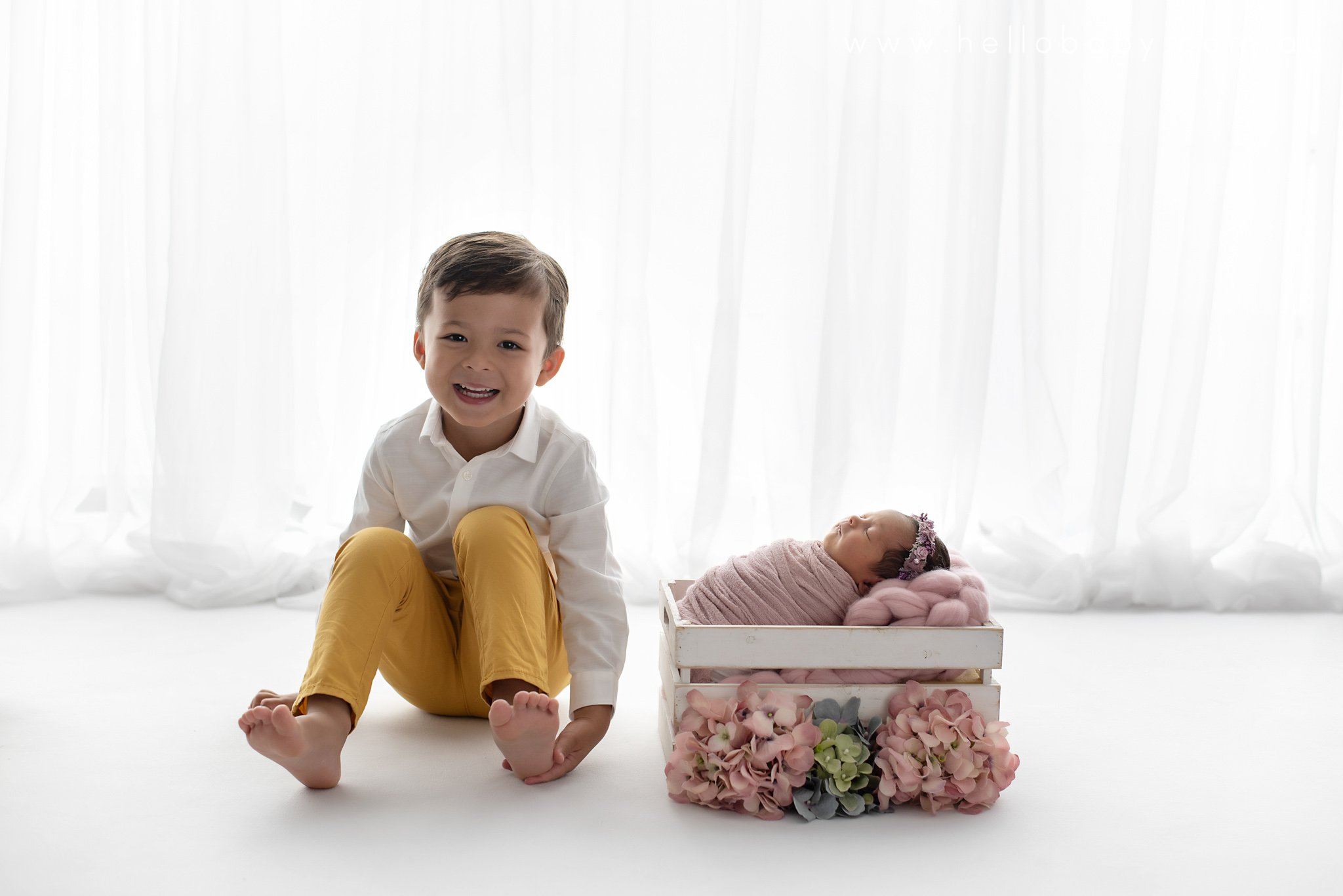 A 3 year old little boy wearing a white shirt and a yellow pair of trousers sitting next to his newborn baby sister who is wrapped in pink and placed in a white basket surrounded by pink and green flowers