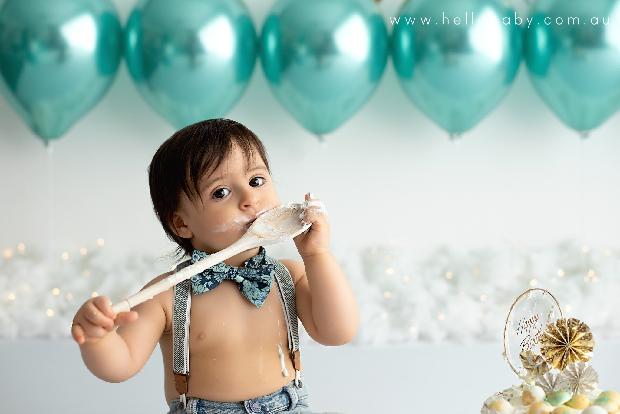 a little boy wearing a pair of jeans and a bow tie sitting on a white floor next to a birthday cake licking a wooden spoon