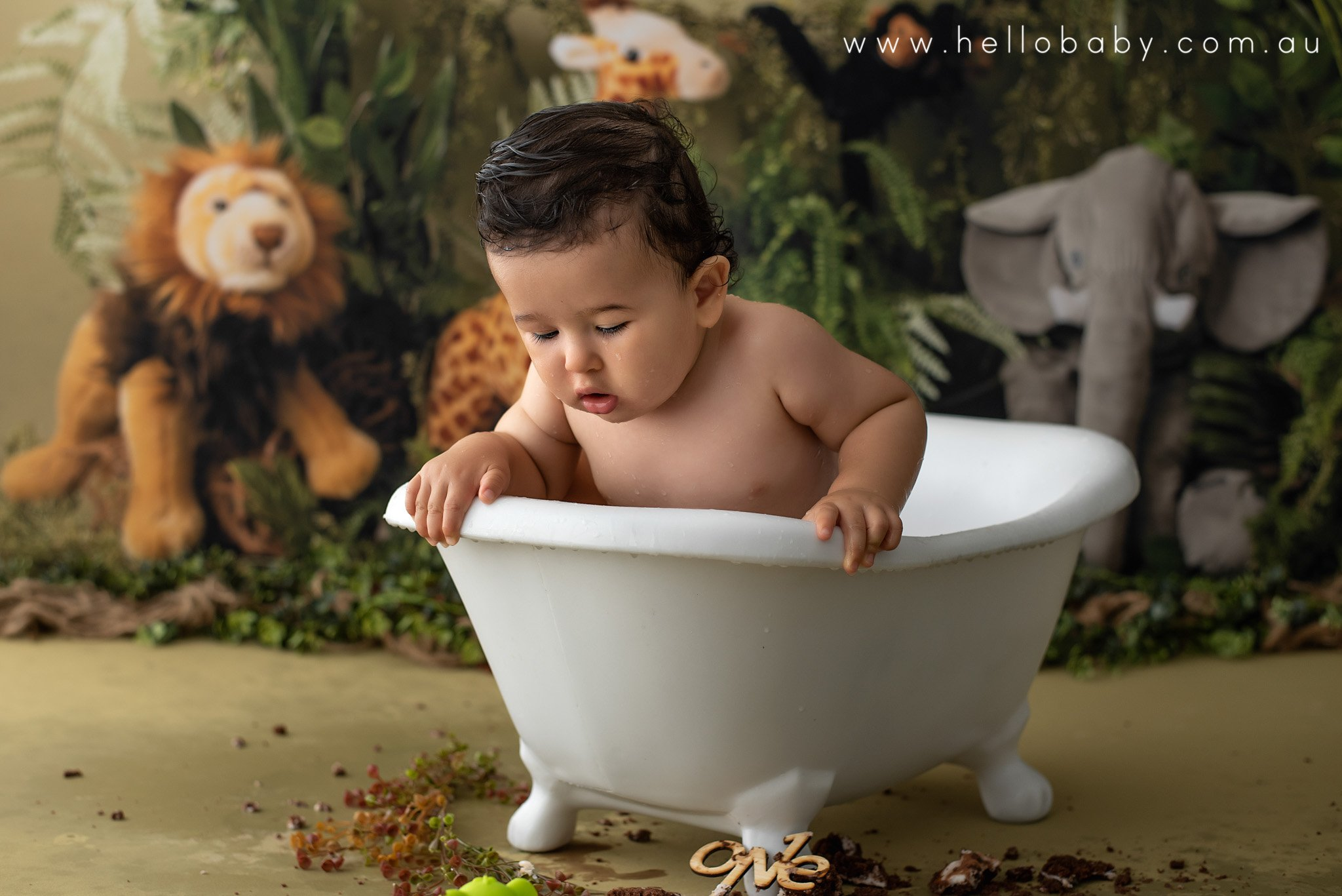 a sweet little boy sitting in a small white baby bath tub looking out onto the ground as if he lost something. It seems his bath toy has fallen out of the bath and he is looking for it trying to pick it up.