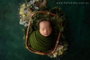 A gorgeous little newborn baby girl sleeping peacefully in a bamboo basket wrapped in a green scarf and wearing a floral headband during her newborn session.