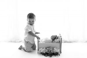 A small child smiling for the camera alongside his baby sister who is sleeping in a tiny baby bed.
