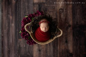 A tiny newborn baby girl wrapped in a red scarf and wearing a red floral headband placed in a basket on dark wooden floor sleeping peacefully during her newborn photography session.