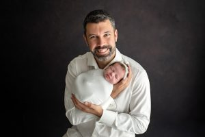 A new father holding his newborn baby smiling for the camera during a newborn session.