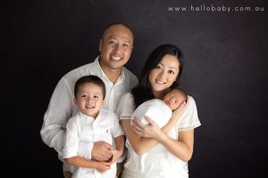 A family of four smiling for the camera during their new baby boy's newborn session