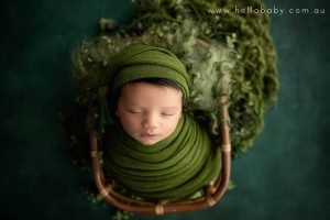 A gorgeous little newborn baby sleeping in a basket wrapped in a green scarf and wearing a matching hat