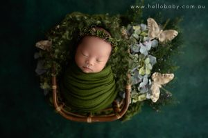 A gorgeous little newborn baby girl sleeping peacefully in a bamboo basket wrapped in a green scarf and wearing a floral headband during her newborn session. The floor the basket is on is a lovely deep green colour. There are some greenery, green and turquoise coloured flowers and golden butterfly decorations next to the basket on the floor.