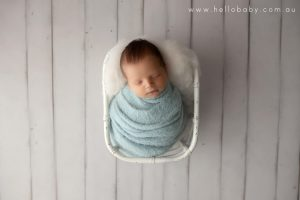 A tiny little newborn baby boy sleeping peacefully in a white bamboo basket on a white wooden floor wrapped in a blue scarf during his newborn session