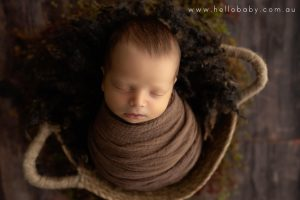 A tiny newborn baby boy wrapped in a brown scarf placed in a basket sleeping peacefully during his newborn photography session