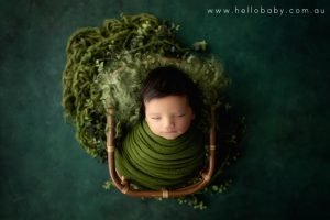 A gorgeous little newborn baby boy with amazing black hair sleeping peacefully in a bamboo basket wrapped in a green scarf during his newborn session