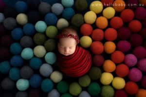 A newborn baby wrapped in red sleeping on a what looks like a pile of cotton balls in rainbow colours.
