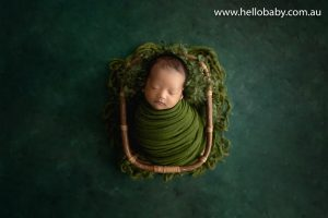 A gorgeous little newborn baby boy sleeping peacefully in a bamboo basket wrapped in a green scarf during his newborn session