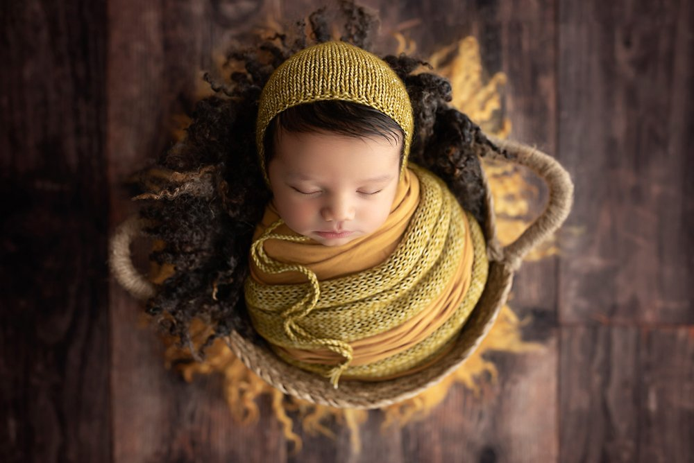 A newborn baby sleeping peacefully in a woven basket, he is wrapped in a mustard coloured scarf and wearing a matching bonnet during a baby shoot.