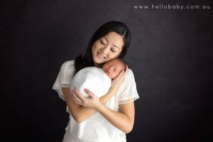 A new mother holding her newborn baby smiling enjoying her cuddle with him during a newborn session