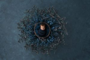 There is a large blue wreath placed on a deep blue backdrop, inside the wreath there is a brown wooden bowl padded with a navy blue fluffy pillow. There is a gorgeous little baby girl sleeping in the bowl, she is wrapped in blue and wearing a matching headband.