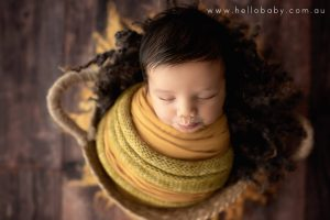 A newborn baby with the most amazing black hear sleeping peacefully in a blanket, he is wrapped in a mustard coloured scarf