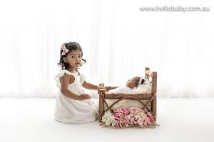 A small child smiling for the camera alongside her baby sister who is sleeping in a tiny baby bed.
