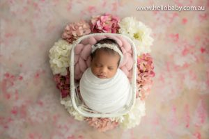Gorgeous little baby girl wrapped in white wearing a white matching headband sleeping peacefully in a white bamboo basket. Inside the basket it's padded with a pink fluffy insert. Alongside the basket there are red and white flowers placed for decorations and the floor is covered in a pink and white flowery backdrop.