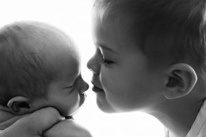 A small child kissing the nose of his newborn baby brother during their photoshoot
