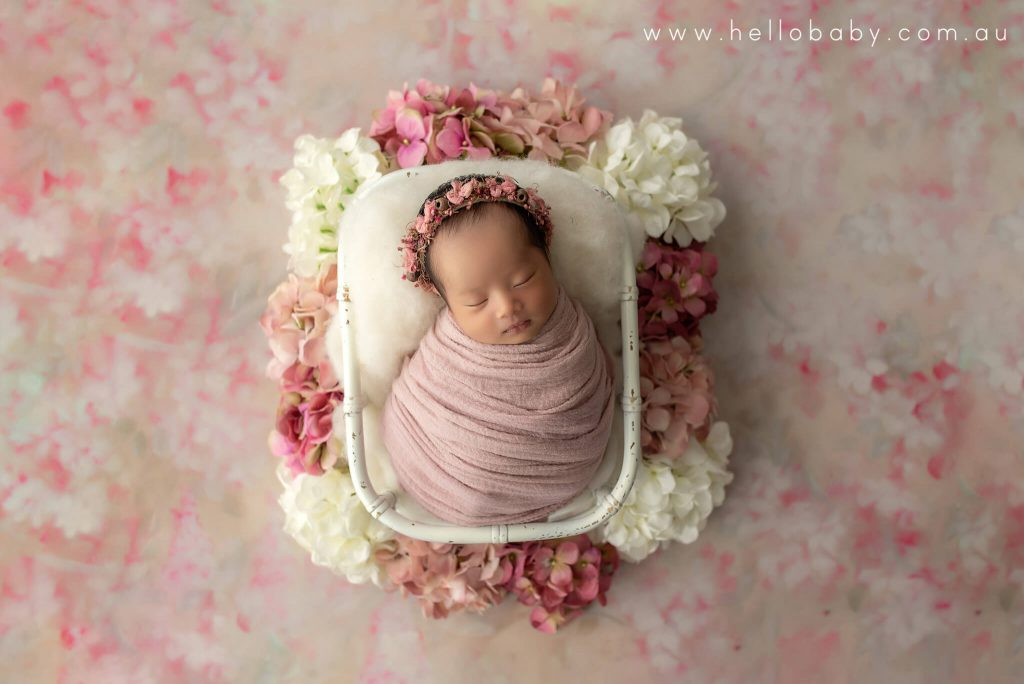 A newborn baby wrapped in a pink scarf placed in a white bamboo basket sleeping peacefully during a photoshoot. Around the basket there are white and pink flower decorations and the there are flowers on the floor as well.